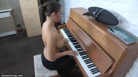 Busty brunette in black pants playing the piano while topless