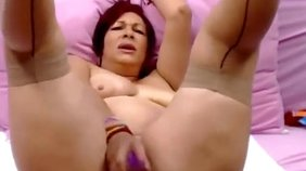 Redhead in flesh-colored stockings fucks her mature pussy with toys