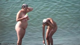 Slim chick talking to her fat girlfriend at a public nudist beach