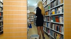 Dress-wearing blonde showing that ass among the bookshelves in HD