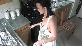 Brunette in an apron-like get-up doing the dishes while looking hot as fuck
